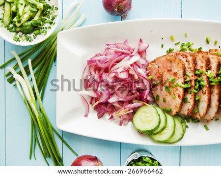 Argentinian Asado pork fillet with pickled onions. Shallow dof. - stock photo