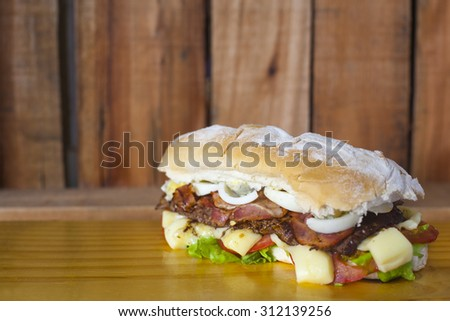 Argentinian beef/steak sandwich, with cheese and vegetables - stock photo