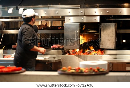 Argentinian chef cooking meat in the restaurant - stock photo
