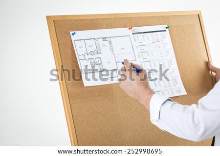 Arhitect checking house blueprint on cork stock photo 252998695 arhitect is checking house blueprint on a cork bulletin board malvernweather Images