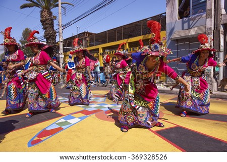 ARICA, CHILE - JANUARY 22, 2016: Tinku dancing group in colourful costumes performing a traditional ritual dance as part of the Carnaval Andino con la Fuerza del Sol in Arica, Chile.  - stock photo