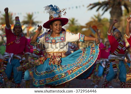 ARICA, CHILE - JANUARY 23, 2016: Tinku dancing group in colourful costumes performing a traditional ritual dance as part of the Carnaval Andino con la Fuerza del Sol in Arica, Chile. - stock photo