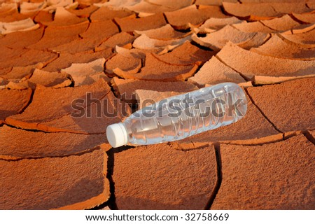 Arid land bottle of water - stock photo