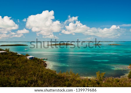 Ariel view of the waters in the bahamas with crystal clear turquoise waters and bright blue sky with puffy white clouds - stock photo