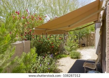 Arizona backyard with automatic retractable awning for extra shade - stock photo