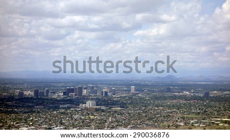 Arizona capital city of Phoenix surrounded by neighboring mountains on a rare cloudy day - stock photo
