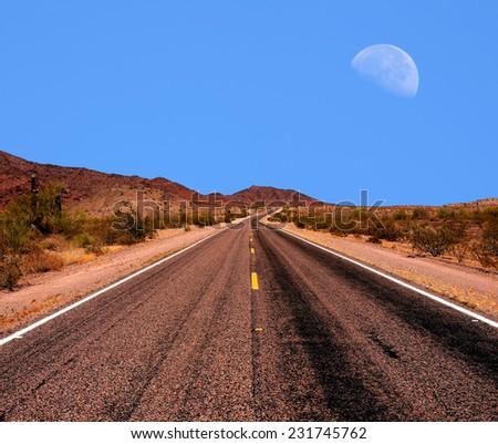 Arizona desert mountain road with moon rising  - stock photo