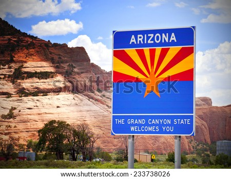 Arizona welcome sign at the state border with red rocks background - stock photo