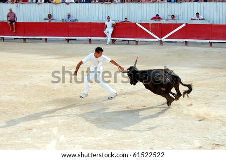 ARLES - JULY 9: Trainees of the school for Raseteur in Arles Daumas fights against a Camargue-bull in the arena on July 09, 2010 in Arles, Bouche du Rhone, France - stock photo