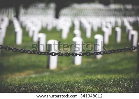 Arlington Cemetery with chain fence graves out of focus - stock photo