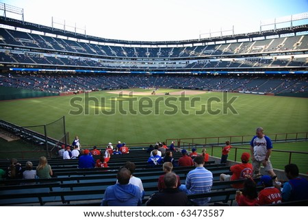 ARLINGTON, TEXAS - SEPTEMBER 27: Fans watch pregame activities at the Ballpark in Arlington before a game between the Rangers and Seattle Mariners on September 27, 2010 in Arlington, Texas. - stock photo
