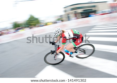 ARLINGTON, VIRGINIA - JUNE 8: A cyclist competes in the elite women's race at the U.S. Air Force Cycling Classic on June 8, 2013 in Arlington, Virginia - stock photo