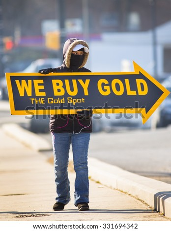 ARLINGTON, VIRGINIA, USA - FEBRUARY 21, 2013: Woman holds We Buy Gold sign on sidewalk to attract customers. - stock photo