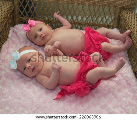 Arm and arm the two little girls hang onto each other for a lifetime of fun - stock photo
