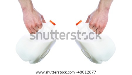 Arm and hand holding plastic milk jug cartons isolated on white background with room for your text. - stock photo