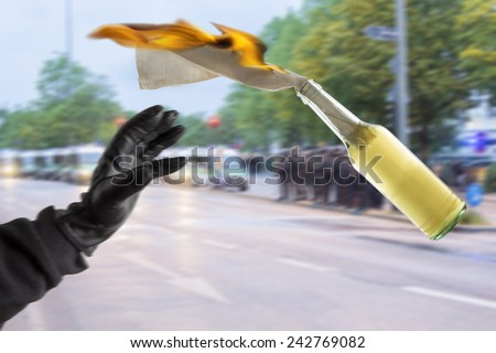 Arm in black sleeve with black leather glove thwowing a Molotov Cocktail with burning fuse, with police forces in the blurred background - stock photo