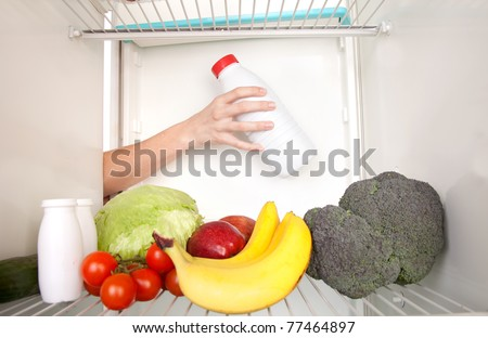 Arm inside refrigerator full of fruit and vegetables.