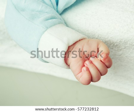 arm of a baby lying in bed at home