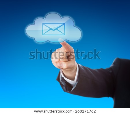 Arm of a corporate person in suit is reaching out to touch a cloud computing symbol containing an email icon. Business metaphor for mobile computing and instant information access. Blue background. - stock photo
