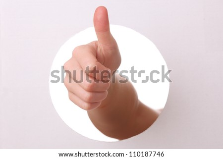 Arm reaches trough a hole with thumbs up - stock photo
