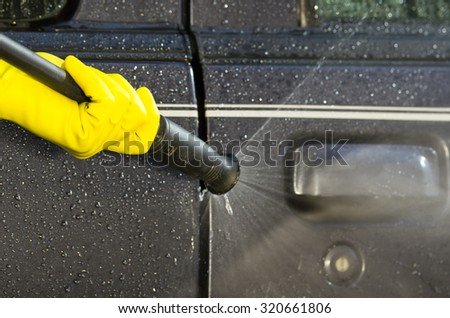 Arm with yellow glove holding high pressure water cleaner and using it on car door windows.