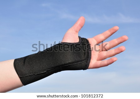 Arm Wrapped in a Black Wrist Brace Against a Blue Sky - stock photo