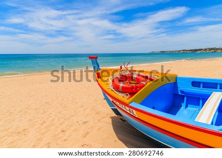 ARMACAO DE PERA BEACH, PORTUGAL - MAY 17, 2015: colorful typical fishing boat on beach in Armacao de Pera coastal village. Algarve region is popular holiday tourist destination on coast of Portugal. - stock photo