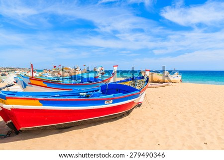 ARMACAO DE PERA BEACH, PORTUGAL - MAY 17, 2015: colorful typical fishing boats on beach in Armacao de Pera coastal village. Algarve region is popular holiday tourist destination on coast of Portugal. - stock photo