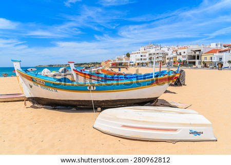 ARMACAO DE PERA BEACH, PORTUGAL - MAY 17, 2015: typical colorful fishing boats on beach in Armacao de Pera coastal town. Algarve region is popular holiday destination in Portugal. - stock photo