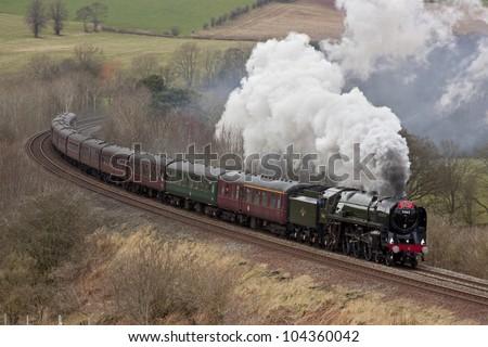 ARMATHWAITE, ENGLAND - FEBRUARY 25: Preserved steam locomotive 70013 Oliver Cromwell heads the Cumbrian Mountain Express through Armathwaite on February 25, 2012, on the Settle to Carlisle railway. - stock photo