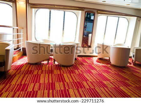 armchair and table close to a window for rest in a cruise ship. - stock photo