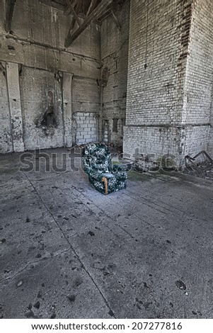 Armchair in an abandoned, ruined factory - stock photo