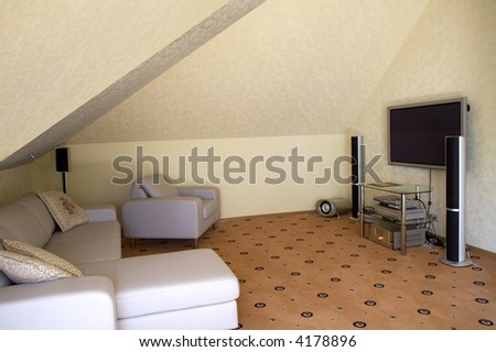 Armchairs, a sofa and a home theater in a modern cottage - stock photo