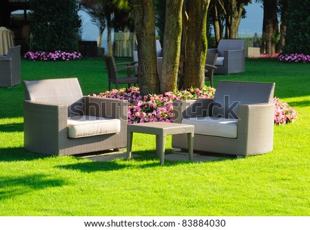 armchairs and table on a green grass