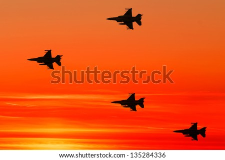 Armed fighter jets on the red sunset background - stock photo