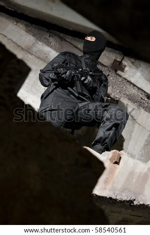 Armed man in black uniform standing on the steps in urban ruins - stock photo
