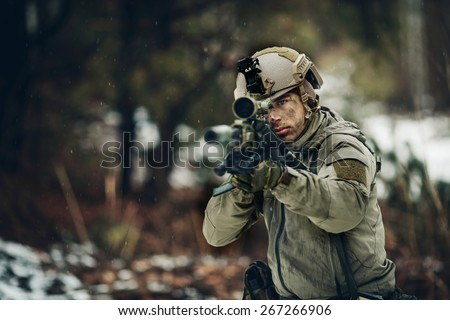 armed  man in camouflage with sniper gun in hands - stock photo
