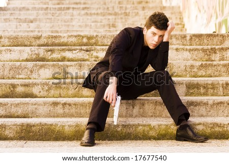 Armed man in stairs - stock photo