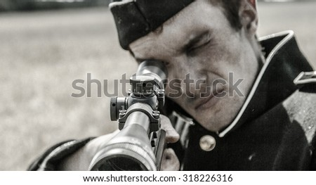 Armed man standing with a gun and aiming.
