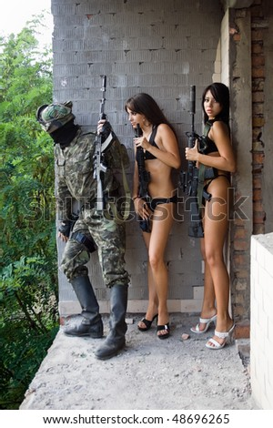 Armed soldier and two women with rifles in ambush