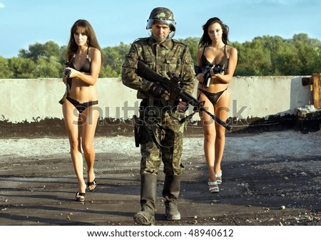 Armed soldier and two young women with rifles - stock photo