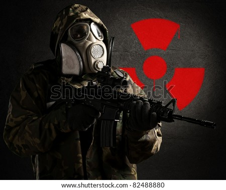armed soldier wearing a gas mask against a concrete wall with red radioactive symbol - stock photo