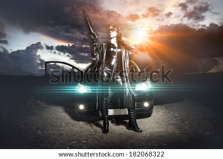 Armed woman with machinegun over cloudy sky - stock photo