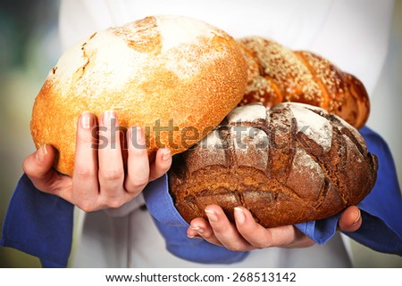 Armful of freshly bread in female hands on light blurred background - stock photo