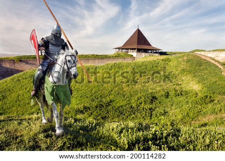 Armored knight on warhorse over old medieval castle (fortress) - stock photo