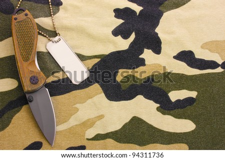 Army badges and knife on camouflage background - stock photo
