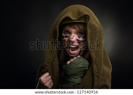 army girl frustrated scream attack, soldier woman cover by masking net military uniform over black background