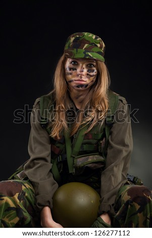 army girl, soldier woman sitting hold helmet wear military camouflage uniform cap over black background