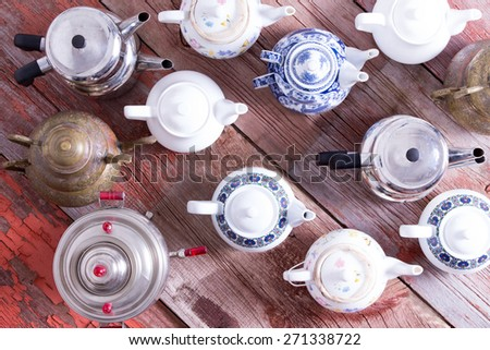 Army of a assorted metal and ceramic Turkish and conventional tea pots arranged in regimental rows all facing the same direction viewed from above on a rustic wood background - stock photo