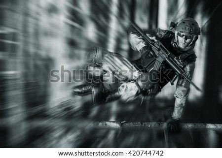 Army Soldier in Action Jumping Over Fallen Tree. Military Concept. - stock photo